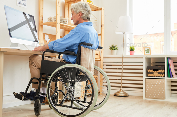 Disabled man using computer at home - Stock Photo - Images