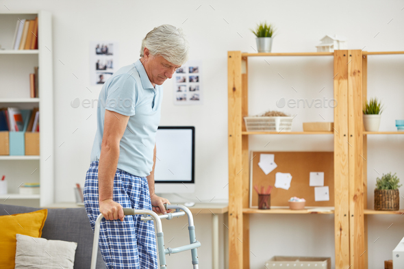 Man learning to walk with walker - Stock Photo - Images