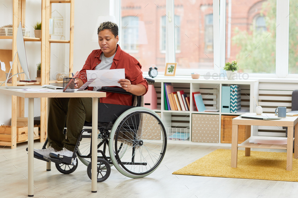 Disabled woman working at her workplace - Stock Photo - Images