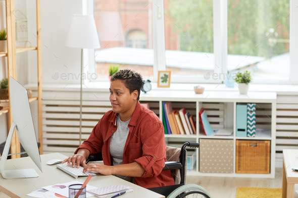 Disabled woman working at office - Stock Photo - Images
