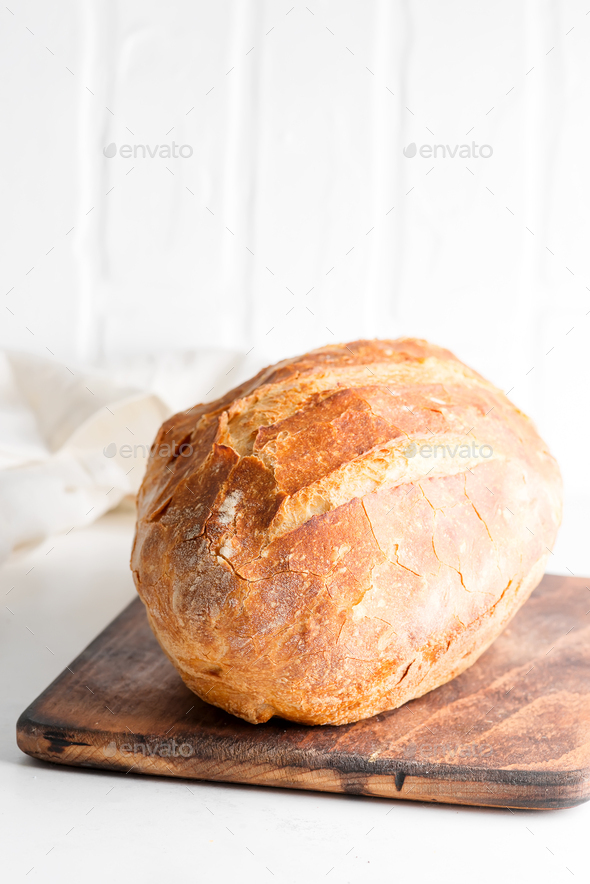 Homemade freshy baked bread on a wooden board and light grey marble table decorated textile towel - Stock Photo - Images