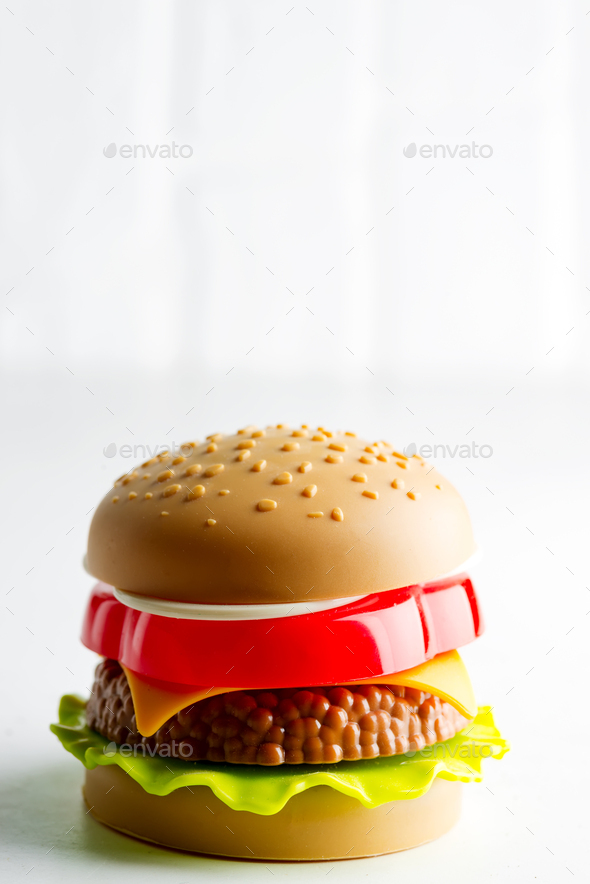 Artificial plastic burger with meat cutlet, tomatoes slice and green salad on a light grey - Stock Photo - Images