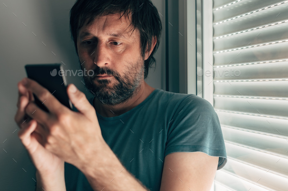 Man text messaging on mobile phone in privacy of bedroom - Stock Photo - Images