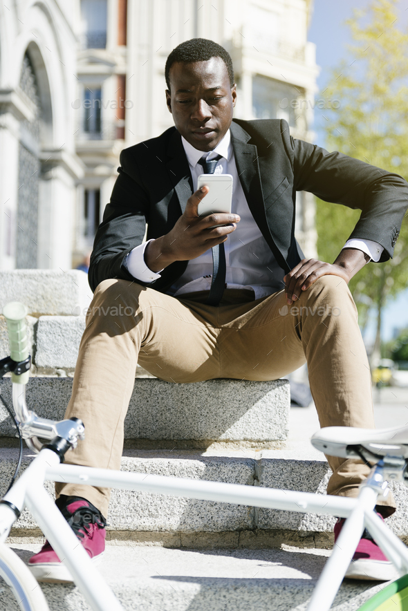 Handsome african man smiling when he is using his mobile. - Stock Photo - Images