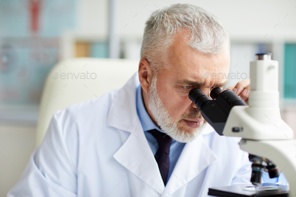 Doctor working with microscope at office - Stock Photo - Images