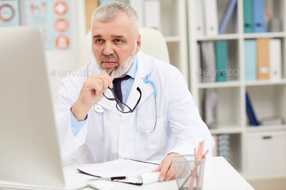 Male doctor working at office - Stock Photo - Images