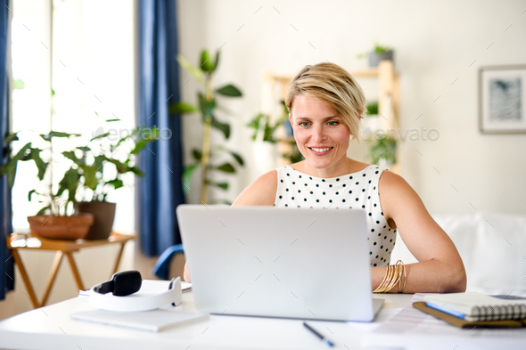 Cheerful young businesswoman with laptop indoors in home office, working - Stock Photo - Images