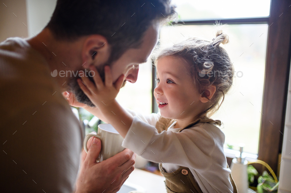 Father giving drink to sick toddler daughter indoors at home - Stock Photo - Images