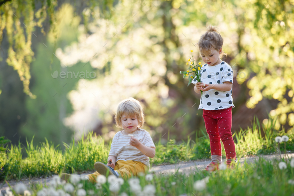 Small children boy and girl playing outdoors in spring nature - Stock Photo - Images