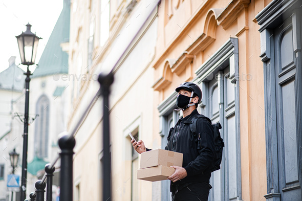 Delivery man courier with face mask and smartphone delivering parcel box in town - Stock Photo - Images