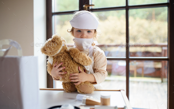 Small toddler girl with doctor uniform indoors at home, playing - Stock Photo - Images
