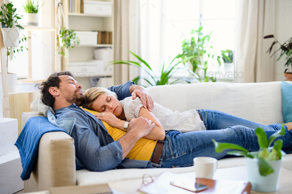Happy couple in love on sofa indoors at home, sleeping - Stock Photo - Images