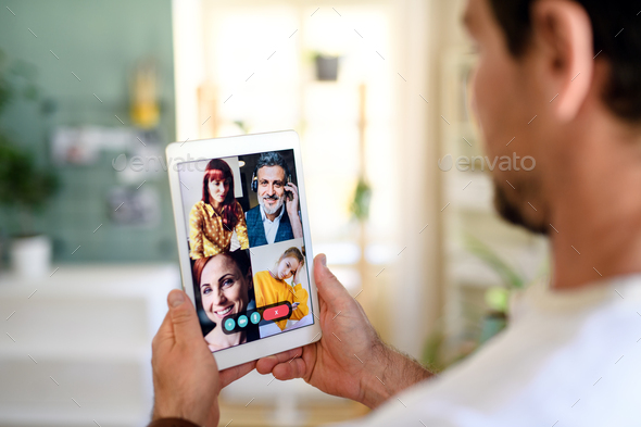 Unrecognizable man having video call on tablet at home - Stock Photo - Images