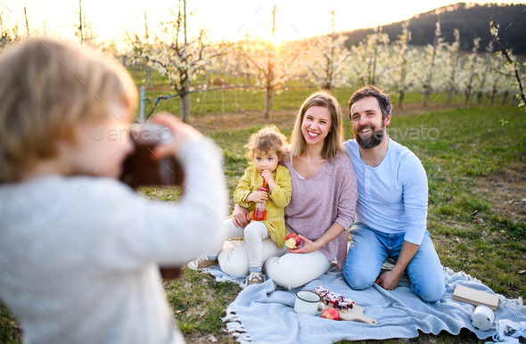 Small boy with camera taking photograph on family picnic outdoors in nature - Stock Photo - Images