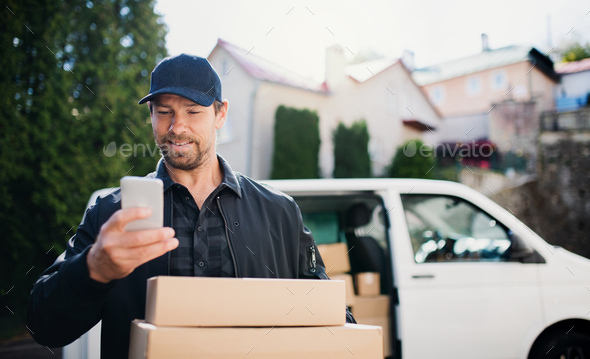 Delivery man courier delivering parcel box in town using smartphone - Stock Photo - Images