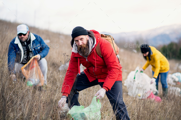 Group of activists picking up litter in nature, environmental pollution concept - Stock Photo - Images