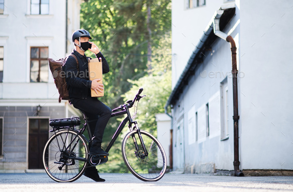 Delivery man courier with face mask and bicycle using smartphone in town - Stock Photo - Images