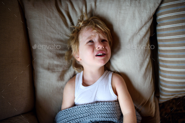 Top view of crying small sick boy in bed indoors at home - Stock Photo - Images