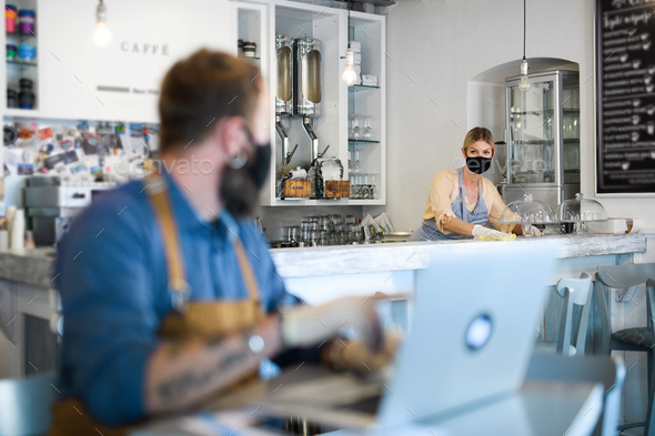 Coffee shop owners working with face masks, open after lockdown quarantine - Stock Photo - Images