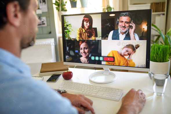 Unrecognizable man having video call on computer at home - Stock Photo - Images