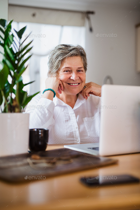 Senior woman with laptop and smartphone working in home office - Stock Photo - Images
