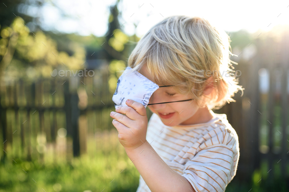 Small boy with face mask playing outdoors, coronavirus concept - Stock Photo - Images