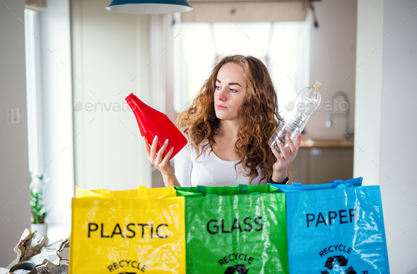 Young woman indoors at home separating glass, paper, and plastic waste - Stock Photo - Images