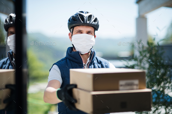 Courier with face mask delivering parcel, corona virus and quarantine concept - Stock Photo - Images