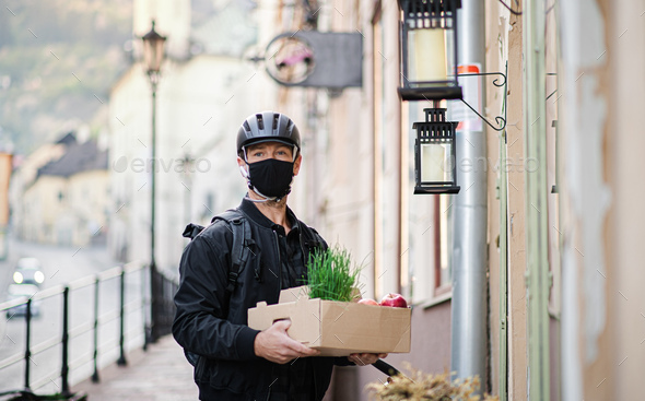 Delivery man courier with face mask delivering groceries in town - Stock Photo - Images