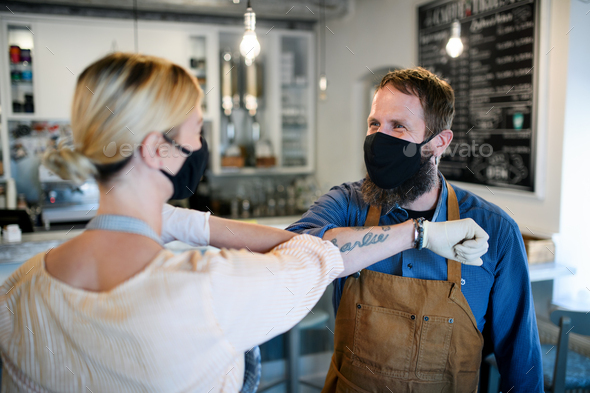 Coffee shop owners with face masks elbow bumping, open after lockdown quarantine - Stock Photo - Images