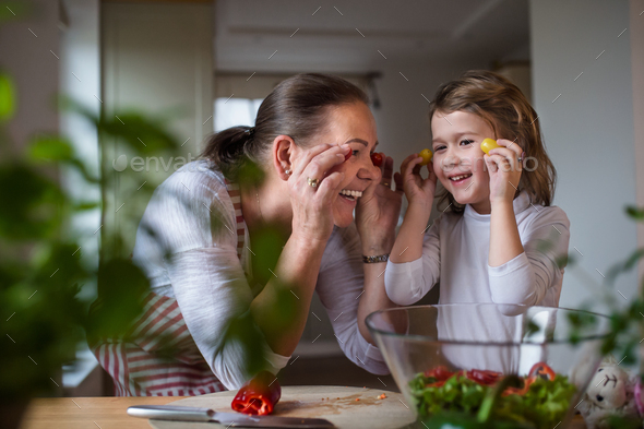 Small girl with senior grandmother in kitchen indoors at home, having fun - Stock Photo - Images