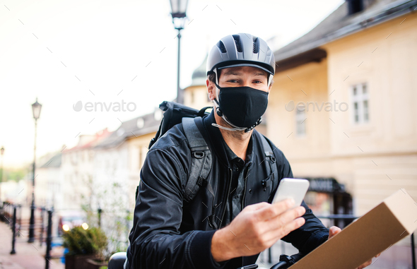 Delivery man courier with face mask and smartphone delivering in town - Stock Photo - Images