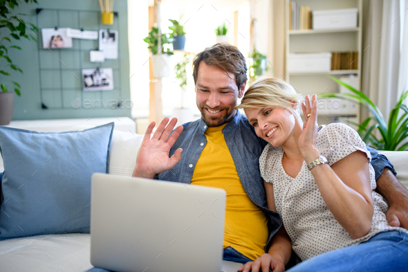 Happy couple having video call on laptop indoors at home, waving - Stock Photo - Images