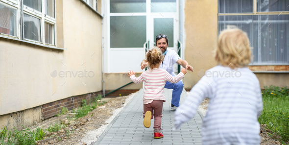 Children running to greet father doctor in front of hospital, end of coronavirus - Stock Photo - Images
