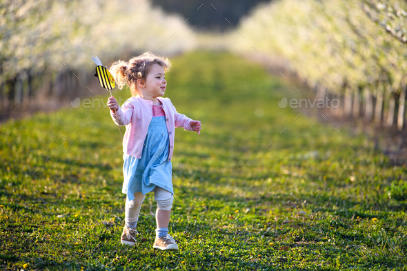 Small toddler girl running outdoors in orchard in spring, holding paper bee - Stock Photo - Images