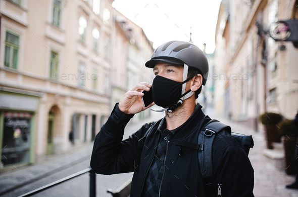 Delivery man courier with face mask and smartphone delivering parcels in town - Stock Photo - Images