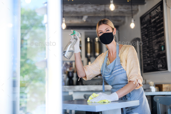 Coffee shop woman owner working with face mask and gloves , disinfecting tables - Stock Photo - Images