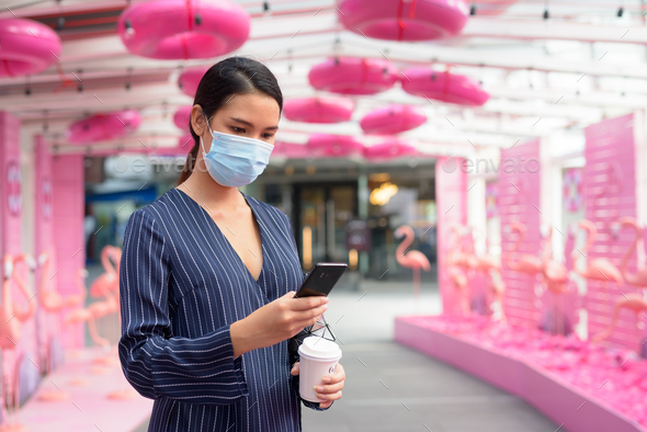 Young Asian businesswoman with mask using phone while having coffee on the go as new normal in the - Stock Photo - Images