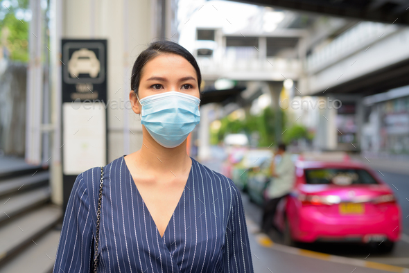 Young Asian businesswoman with mask waiting at the taxi station in the city streets - Stock Photo - Images