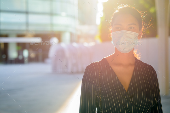 Young Asian businesswoman with mask for protection from corona virus outbreak in the city outdoors - Stock Photo - Images