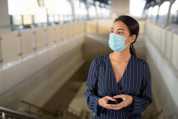 Young Asian businesswoman with mask thinking while going up the skytrain station - Stock Photo - Images