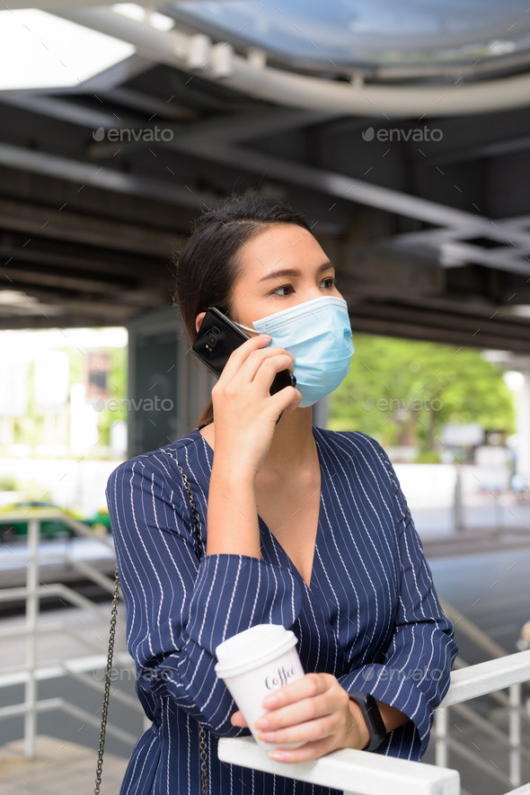 Young Asian businesswoman with mask talking on the phone while having coffee on the go as the new - Stock Photo - Images