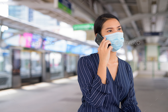Young Asian businesswoman with mask talking on the phone while sitting at the skytrain station - Stock Photo - Images