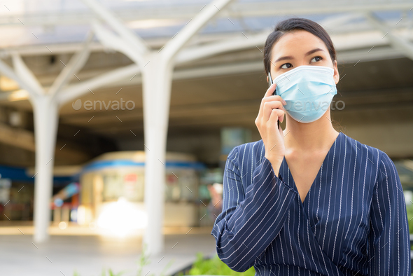 Young Asian businesswoman with mask for protection from corona virus outbreak talking on the phone - Stock Photo - Images