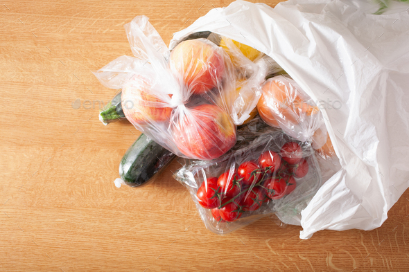 single use plastic waste issue. fruits and vegetables in plastic bags - Stock Photo - Images