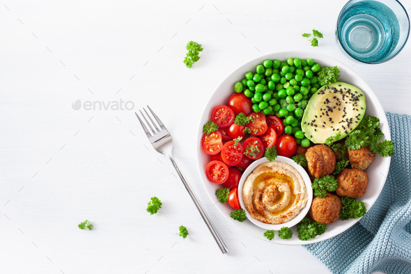 healthy vegan lunch bowl with falafel hummus tomato avocado peas - Stock Photo - Images