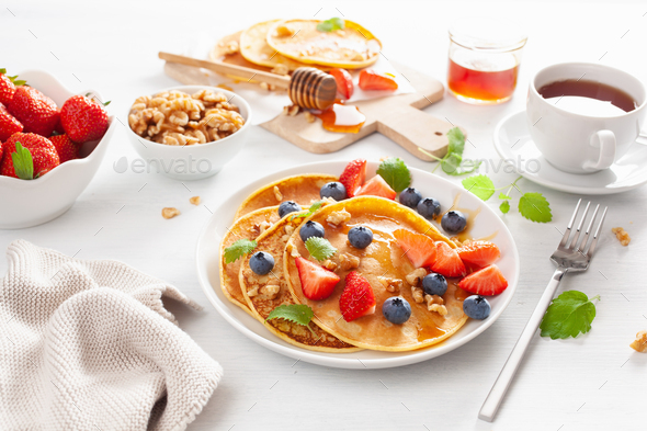 pancakes with blueberry strawberry honey and nuts for breakfast - Stock Photo - Images