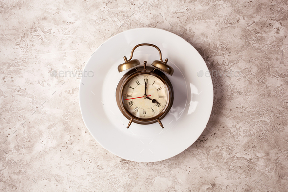 concept of intermittent fasting, ketogenic diet, weight loss. alarmclock on plate - Stock Photo - Images