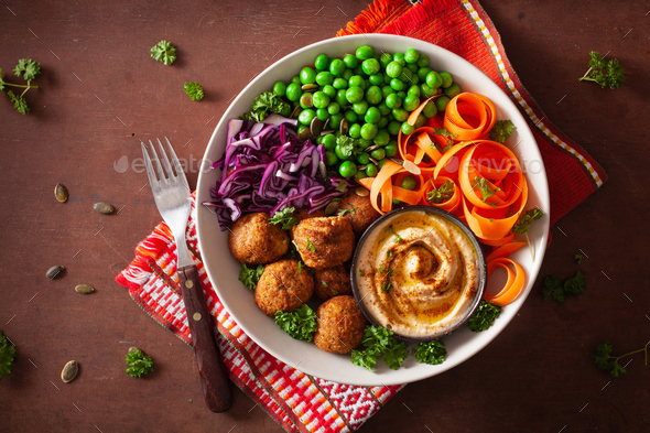 healthy vegan lunch bowl with falafel hummus carrot ribbons cabbage and peas - Stock Photo - Images