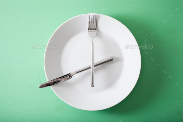 concept of intermittent fasting and ketogenic diet, weight loss. fork and knife crossed on a plate - Stock Photo - Images